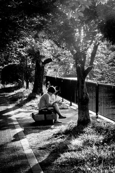 A woman reads by the canal in Kyoto, Japan