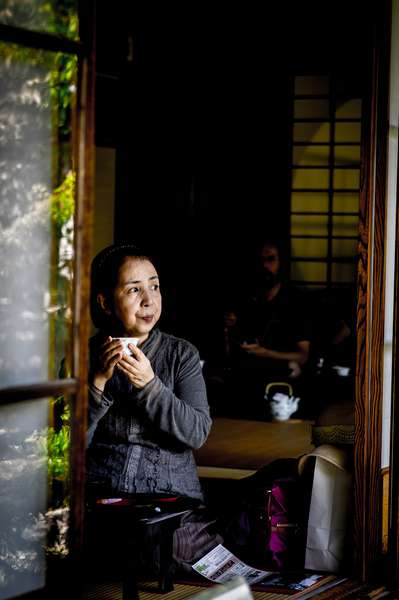 A woman sips tea at a teahouse in Kyoto