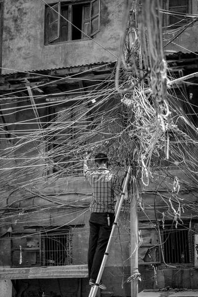 A man fixes a mass of cabling in Kathmandu, Nepal