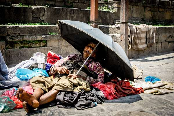 An old woman tries to sleep in the sun in Kathmandu, Nepal
