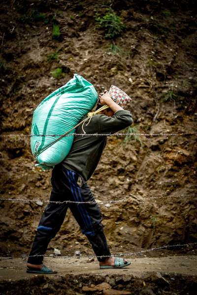 A porter carries rice through a village, Nepal
