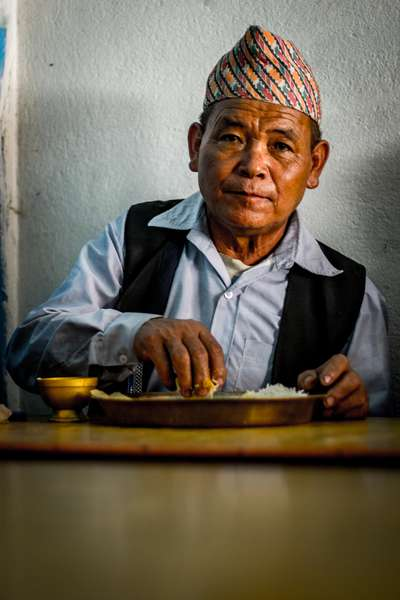 A man lunches on dhal bhat, Nepal