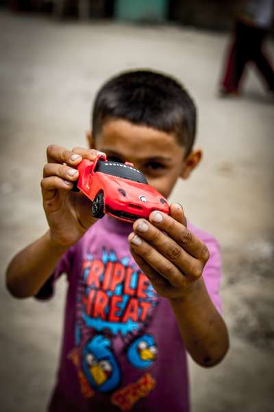A boy shows off his toy car in Kathmandu, Nepal