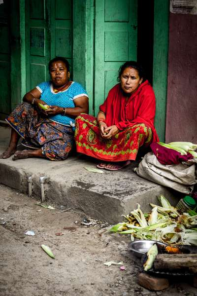 Women sit in a doorway in Kathmandu, Nepal
